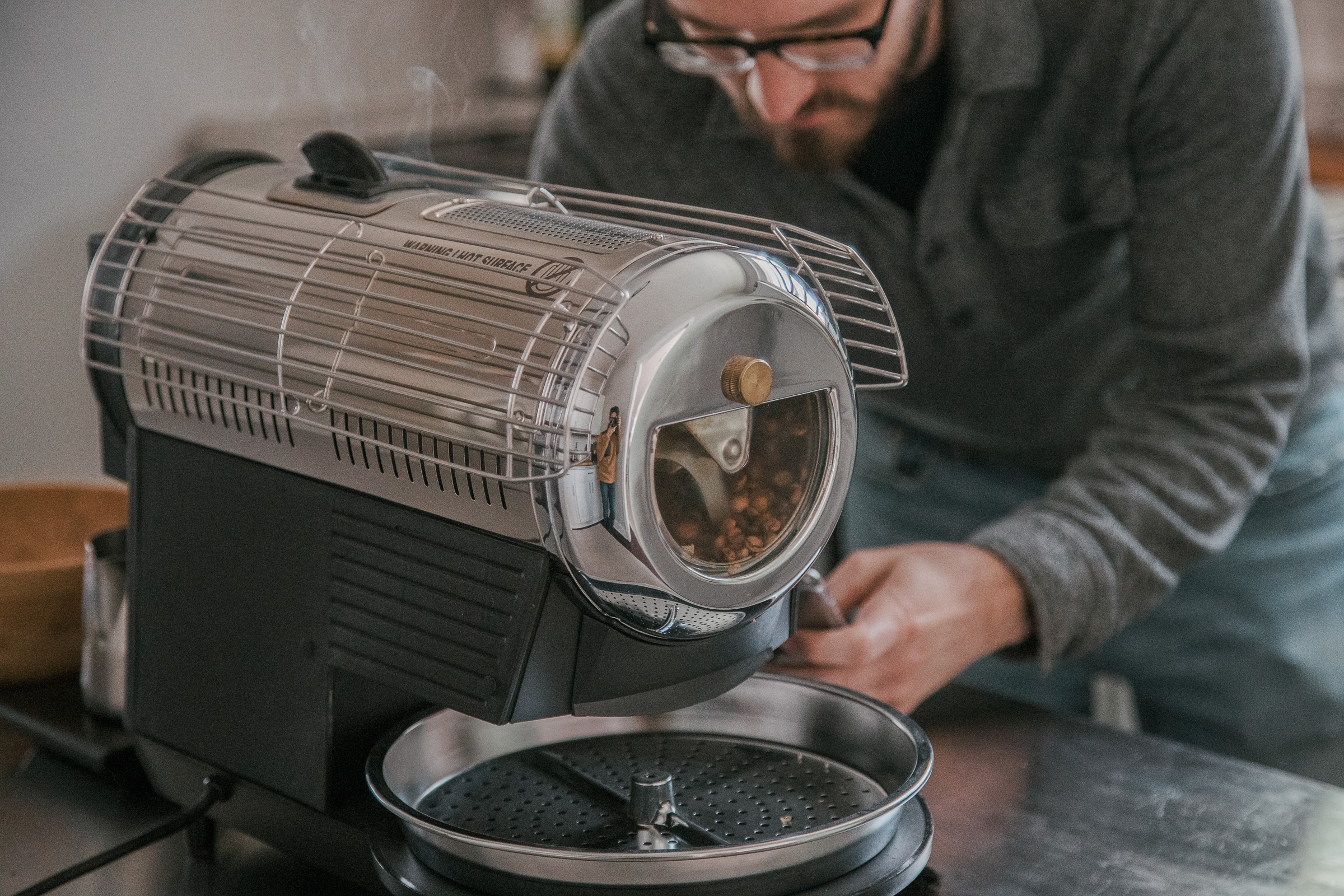 A person looking at their stopwatch, getting ready to make adjustments to the Hottop Coffee Roaster.