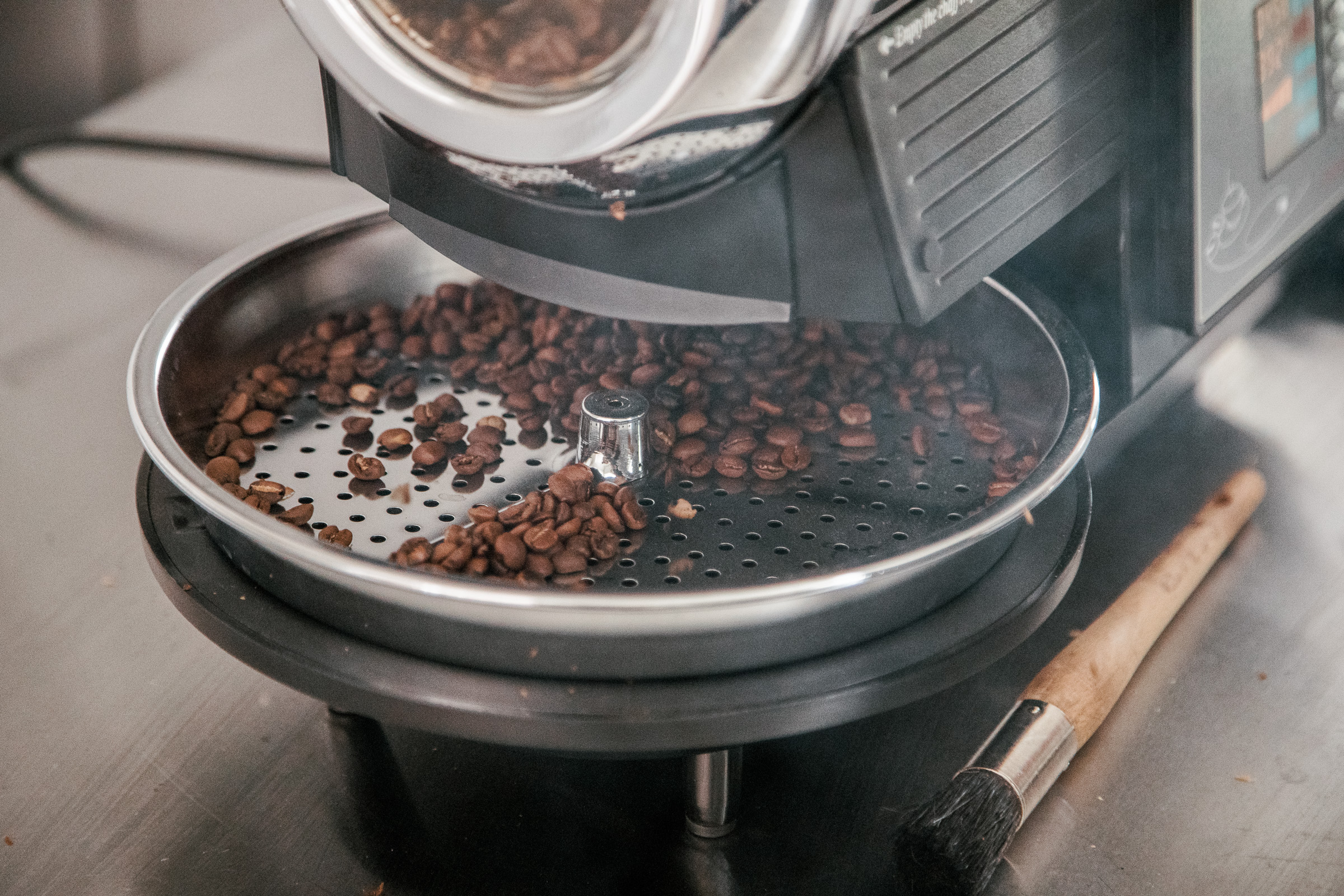 A closeup of the Hottop Coffee Roaster's cooling tray, while beans are dropping from the roasting chamber with smoke billowing out.