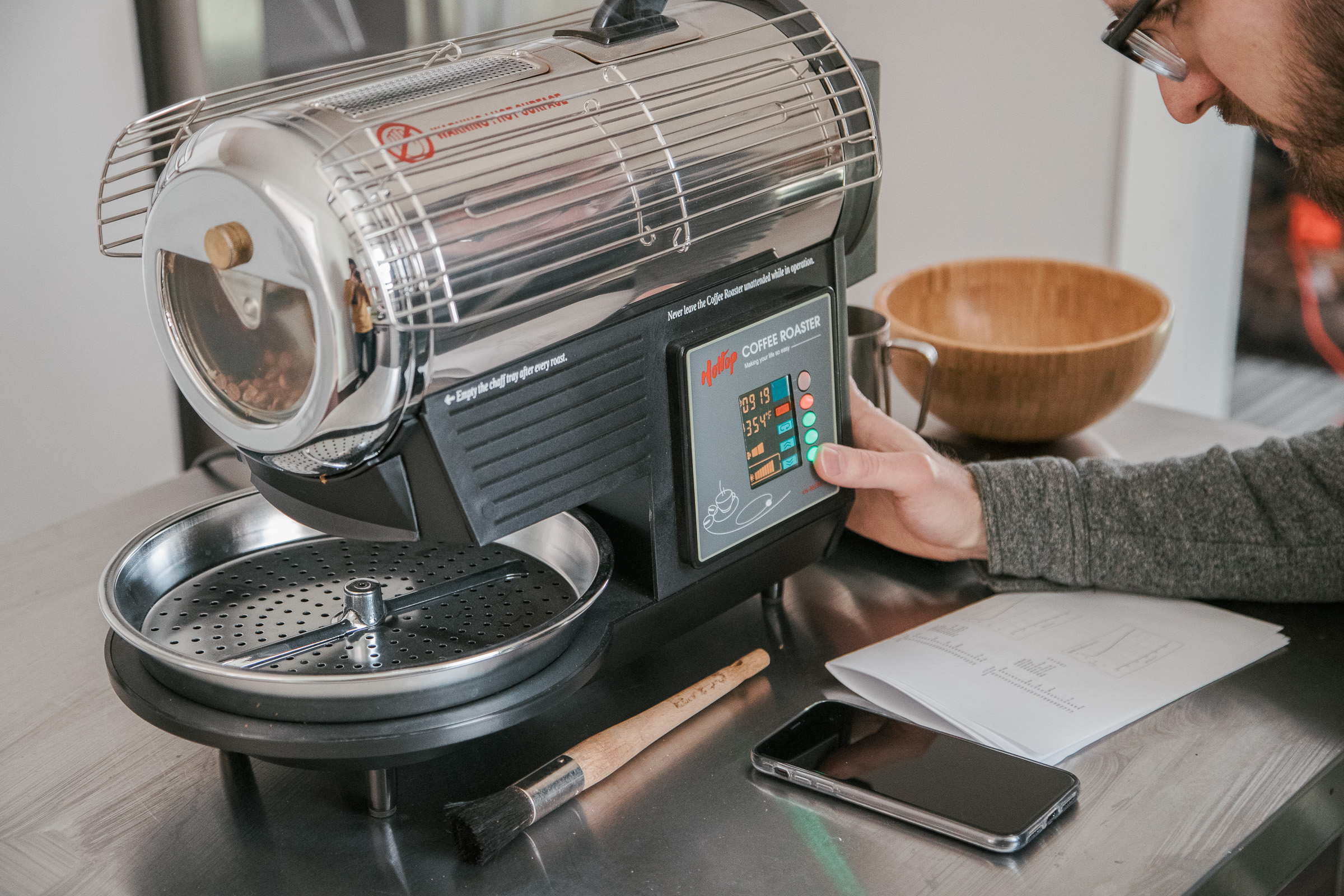 A person changing the settings on a Hottop Coffee Roaster during a roast.