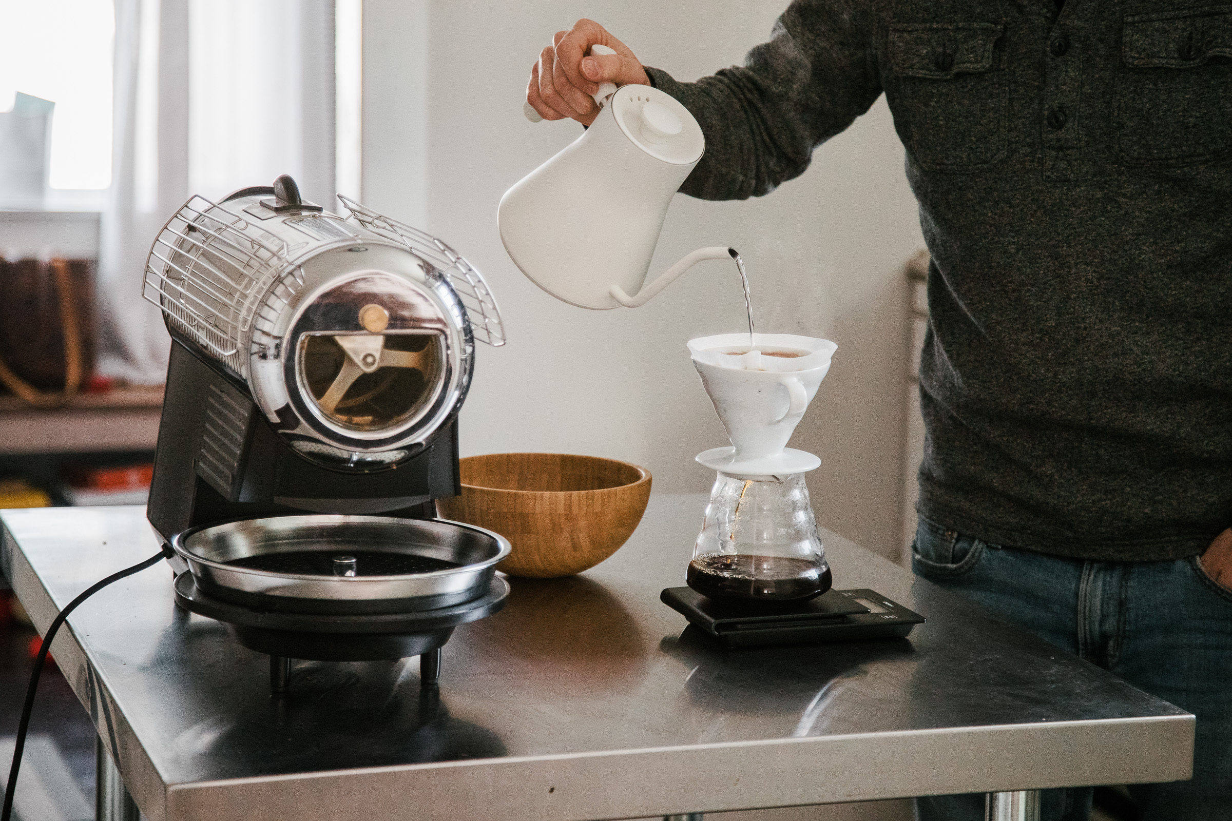 A person brewing coffee with a Hario V 60 pour over brewer next to a Hottop Coffee Roaster.