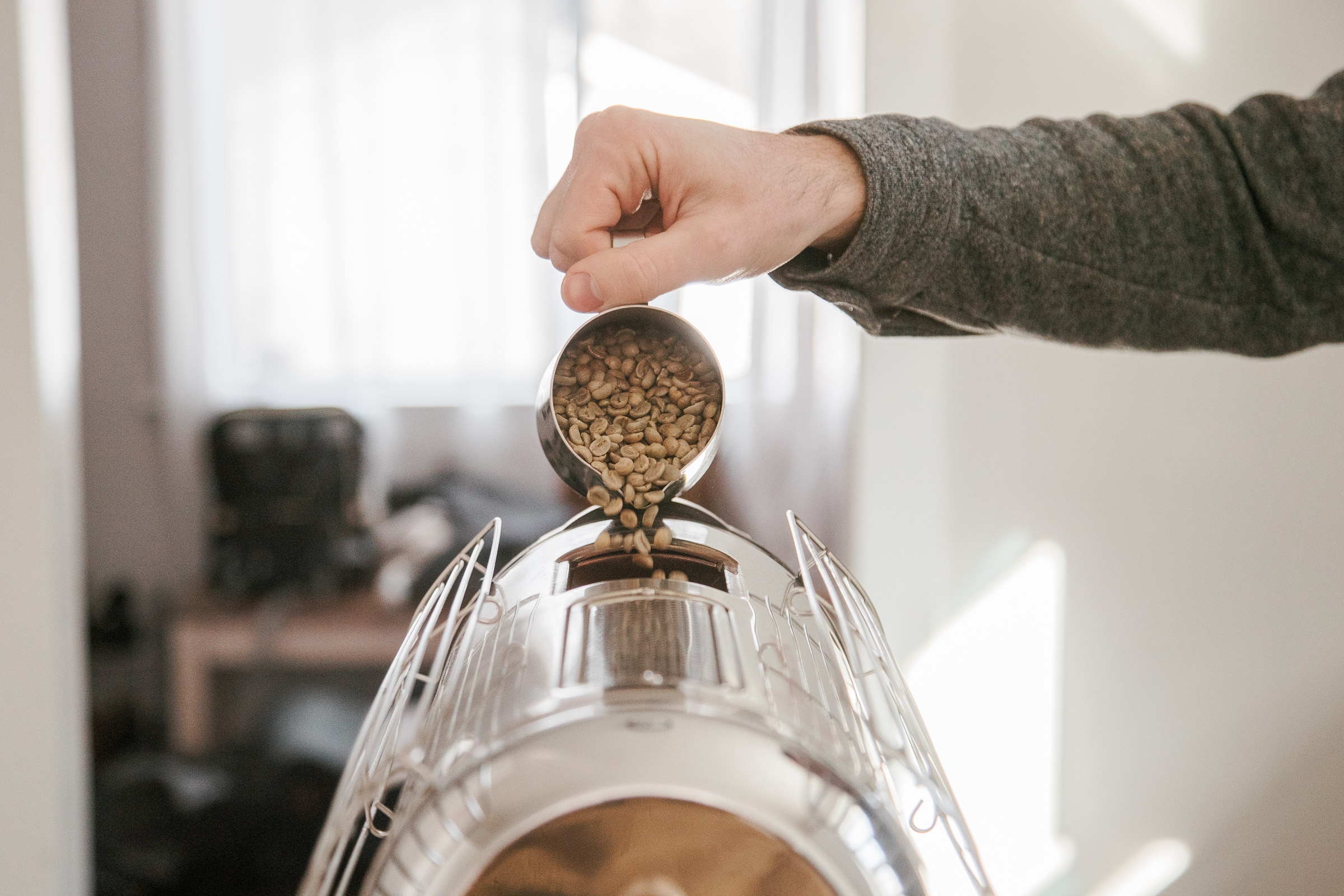 A person pouring the unroasted coffee beans into the top of the Hottop Coffee Roaster with a latte art pitcher.