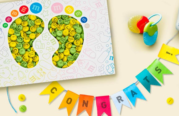 Personalized M&M'S congratulations gift with custom messages in a gift box with die cut baby feet on a table with baby decorations