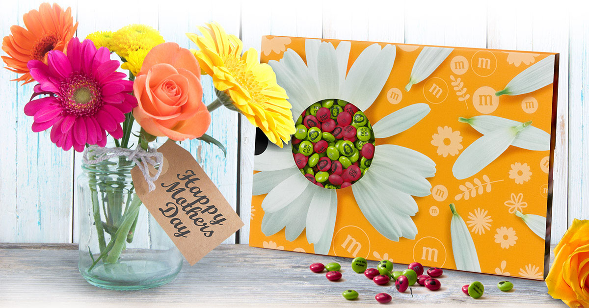 Personalized Mother's Day gift M&M'S in a flower-themed box next to a vase of flowers