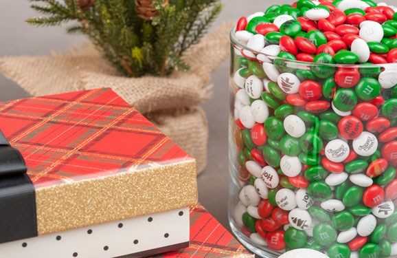 Personalized Christmas M&M'S in a large glass serving dish with wrapped Christmas gifts