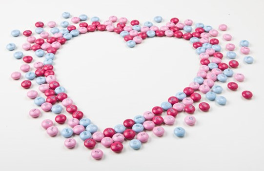 Pink, red, and blue customized M&M'S arranged on a white background in the shape of a heart