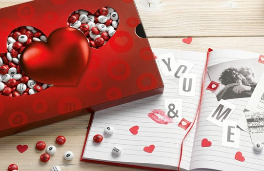 Personalized Valentine's Day gift M&M'S in a heart themed bo next to an open book