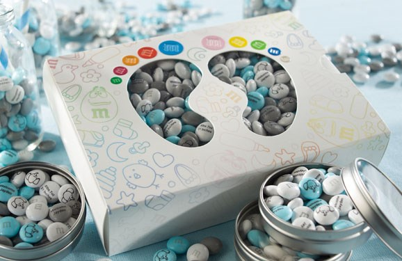 A new baby gift of blue, silver, and white personalized M&M'S in metal tins and in a box with die cut windows in the shape of baby feet