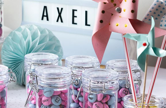 Pink and blue personalized M&M'S in glass jars with flip-top lids next to paper pinwheels