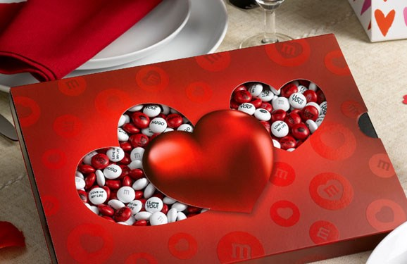 Red and white M&M'S with custom messages in a die-cut heart themed gift box and champagne flutes on a dining table