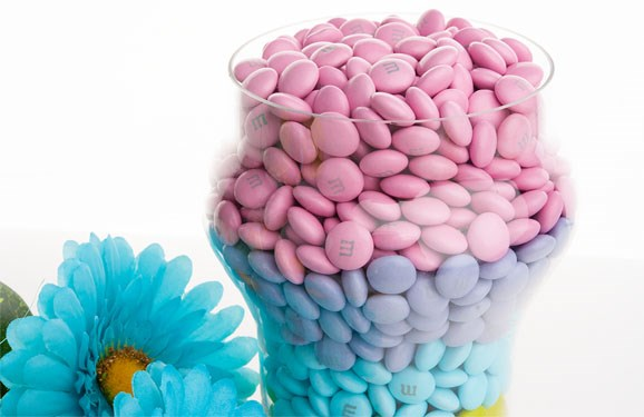 Personalized Easter candy M&M'S inside a glass container next to flowers