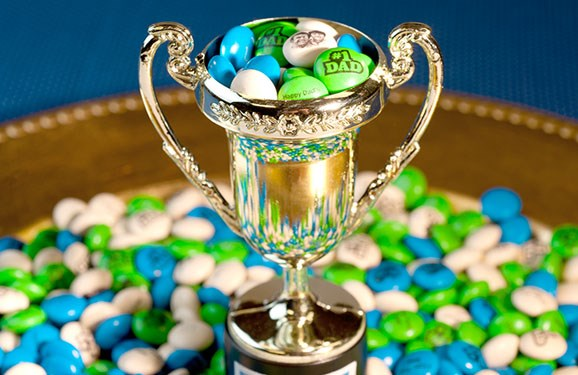 Personalized M&M'S inside of and surrounding a small silver trophy