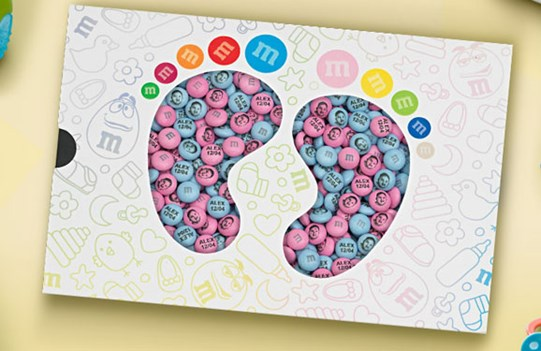 Blue and pink customized M&M'S in a gift box with die cut window in the shape of baby feet, surrounded by baby clothes and toys