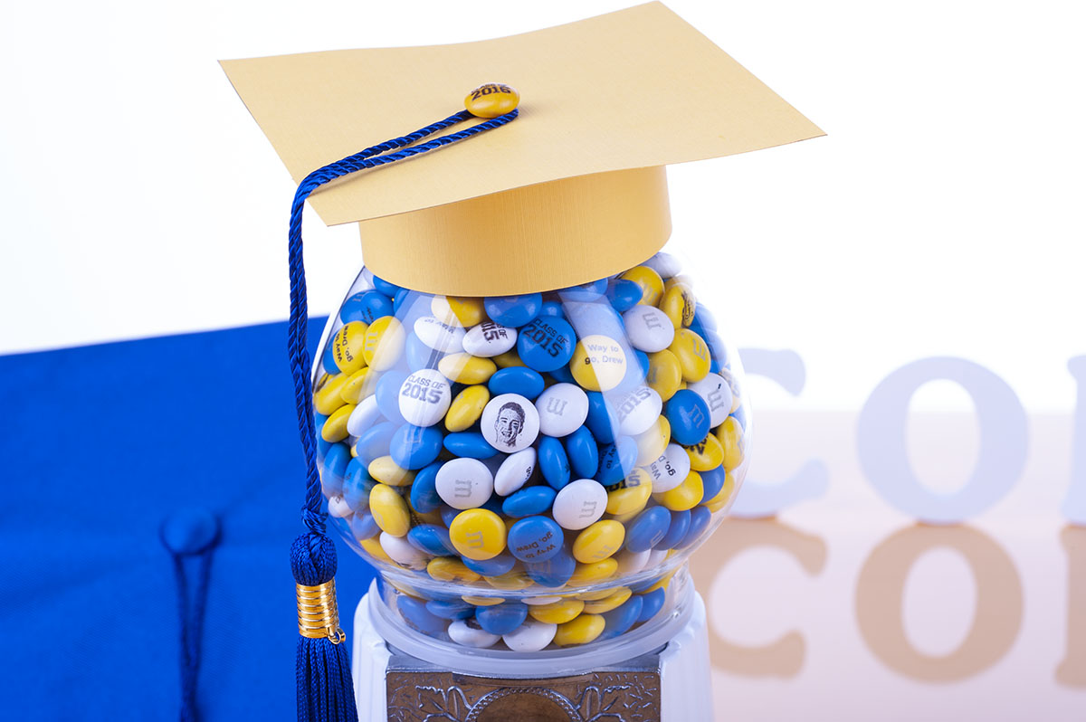 Personalized M&M'S in a clear plastic container with a graduation cap on top