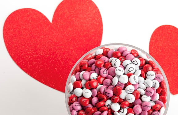 Personalized Valentine's Day gift M&M'S in a glass bowl on a white background with red hearts