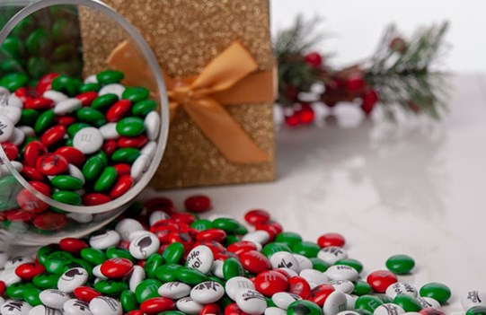 Red, green, and white Christmas M&M'S in a glass serving bowl with holiday decorations