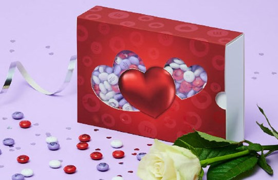 Light purple, white, and red personalized M&M'S in a die-cut heart themed gift box next to a white rose