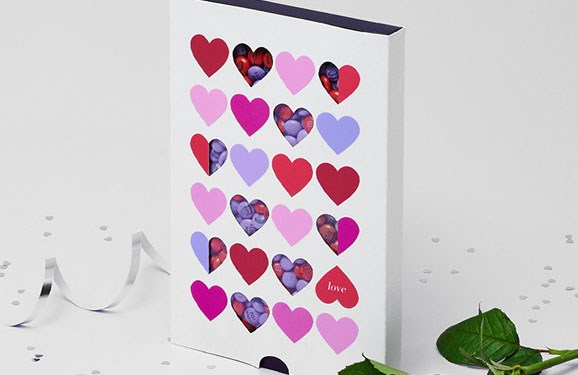 Light purple and red customized M&M'S in a gift box with die-cut windows and heart designs on the front next to a white rose