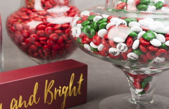Personalized Christmas M&M'S in a candy dish next to a Merry and Bright holiday sign
