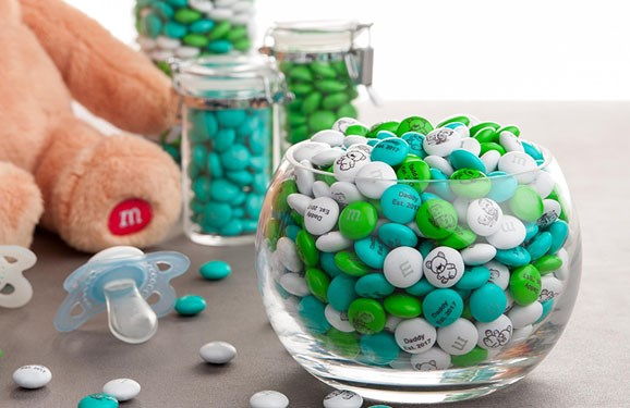 Personalized M&M'S in clear glass containers next to a teddy bear