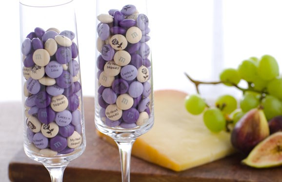 Purple, light purple, and cream colored customized M&M'S in two champagne flutes in front of cheese and fruit on a cutting board