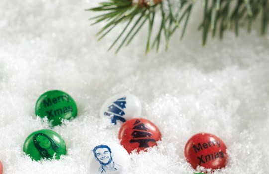 Green, red and white customized M&M'S in a snowy Christmas setting with an ornament