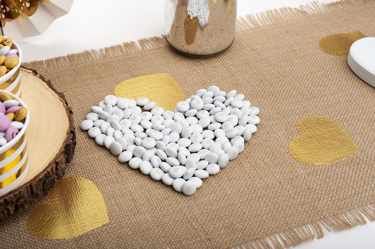 White personalized M&M'S arranged on a table in the shape of a heart