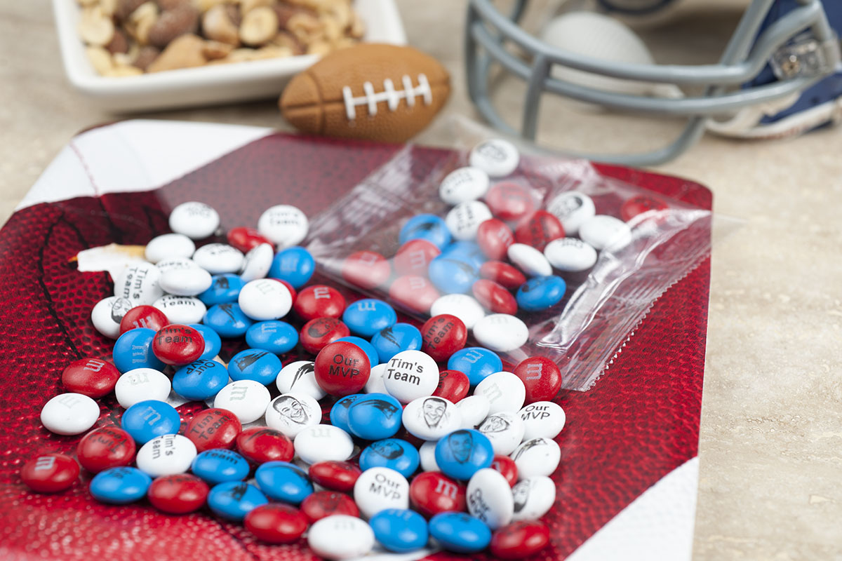 Personalized Father's Day gift M&M'S on a table and in a clear bag with football in the background