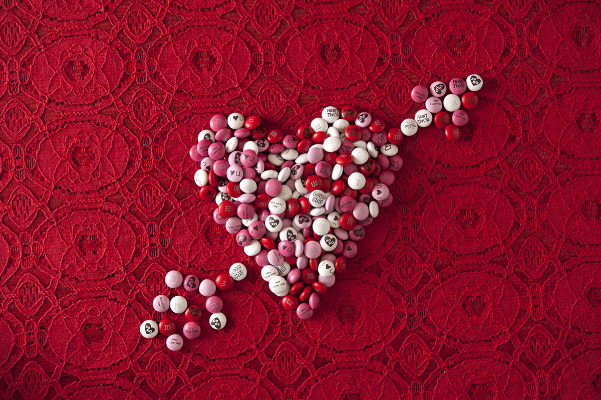 Personalized M&M'S in the shape of a heart with an arrow through it on a red background