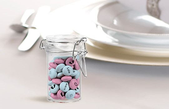 A fancy dinner table setting for one with a small jar of pink and blue personalized M&M'S and a placeholder with a name and date