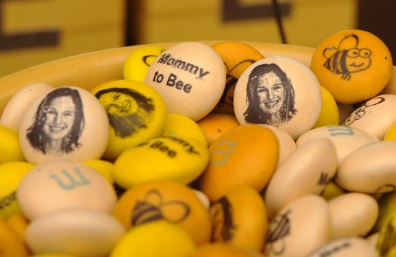 Orange, yellow, and cream personalized M&M'S baby shower candy in an orange pot