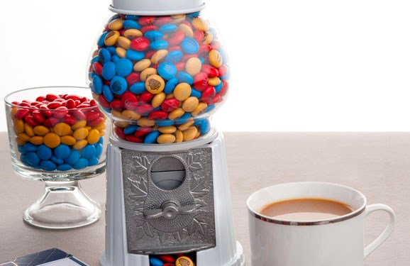 Personalized M&M'S in a traditional gumball machine on a table
