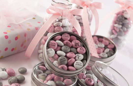Pink, silver, and white personalized M&M'S in metal tins with clear plastic lids and in glass jars with pink ribbons