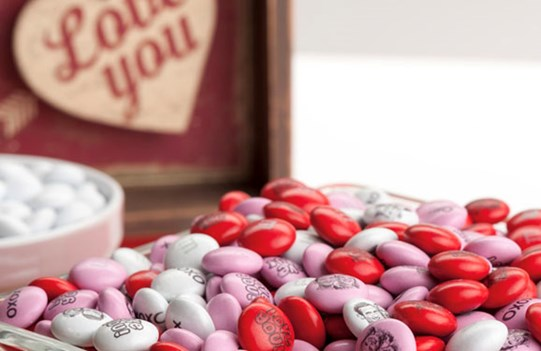 "Personalized M&M'S in glass serving dishes and a sign reading ""I love you"""