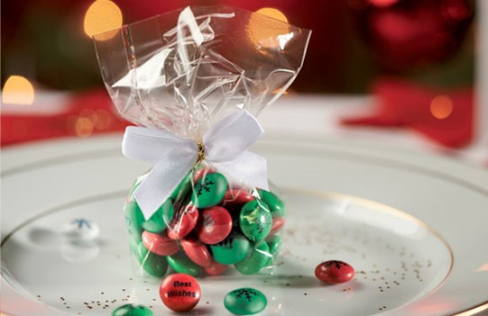 Red and green M&M'S in a cellophane gift bag on a Christmas dinner plate