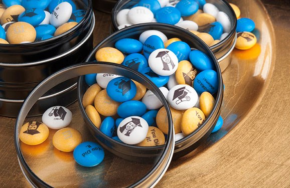 Personalized graduation gift M&M'S in round silver tins with clear tops next to a graduation cap