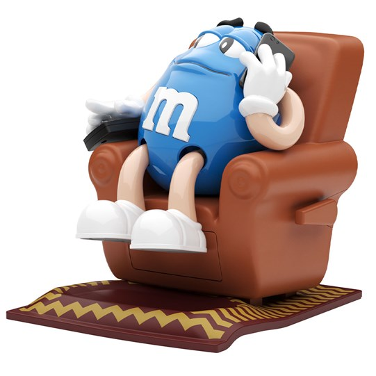 M&M'S Recliner Dispenser, Side View of Blue M&M'S Character Lounging on Chair Holding TV Remote.