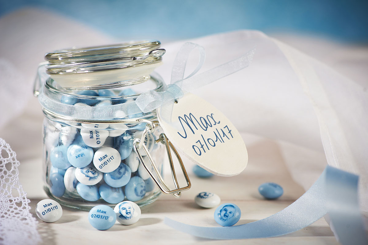 Blue and white personalized M&M'S in a flip-top glass jar and a tag with a child's name and birthdate