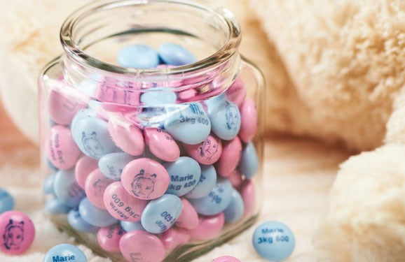 Pink and blue personalized M&M'S in a glass jar next to a stuffed teddy bear with a pink ribbon