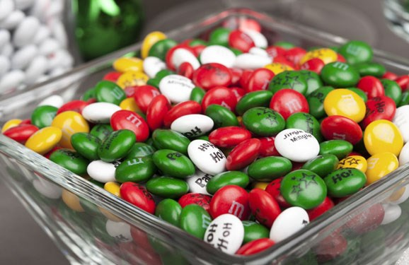 Red, green, yellow, and white Christmas M&M'S in a square glass serving bowl