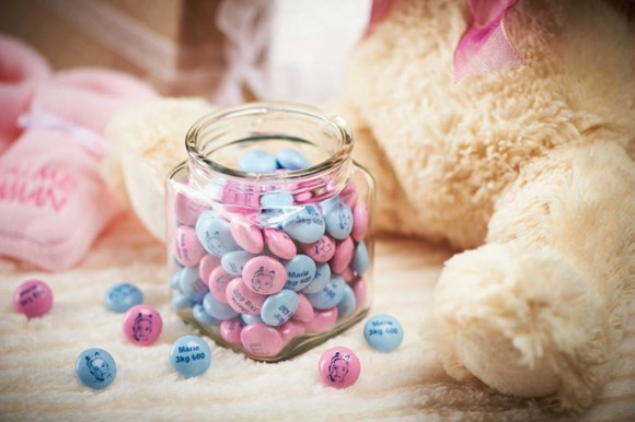 Pink and blue personalised M&M'S in a glass jar next to a stuffed teddy bear with a pink ribbon