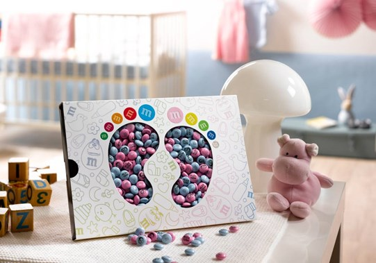 A new baby gift of blue baby and pink personalised M&M'S in a box with die cut windows in the shape of baby feet