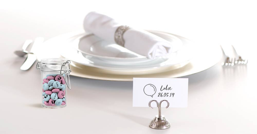 A fancy dinner table setting for one with a small jar of pink and blue personalised M&M'S and a placeholder with a name and date