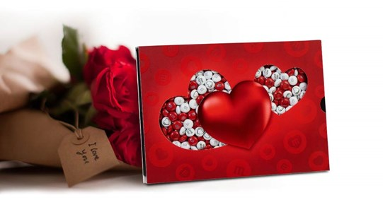 White, and red personalised M&M'S in a die-cut heart themed gift box next to red rose