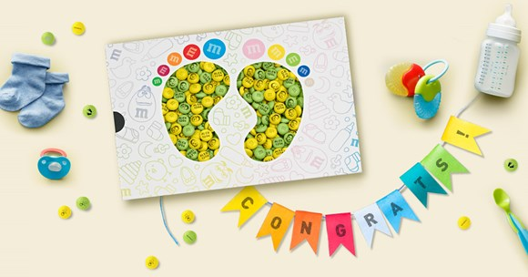 Personalised M&M'S congratulations gift with custom messages in a gift box with die cut baby feet on a table with baby decorations