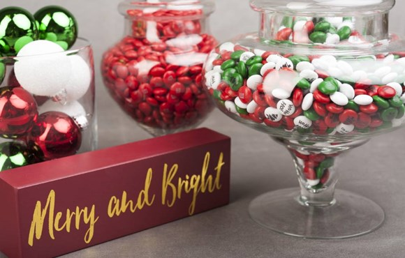Personalised Christmas M&M'S in a candy dish next to a Merry and Bright holiday sign