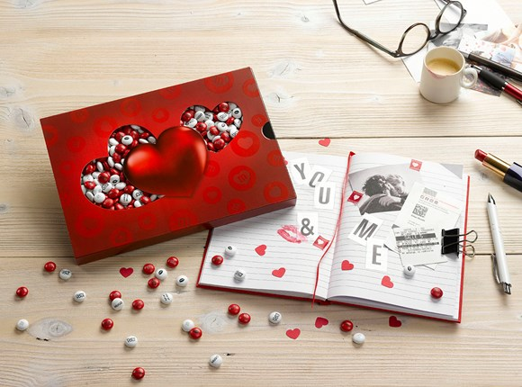 Personalised Valentine's Day gift M&M'S in a heart themed box next to an open book