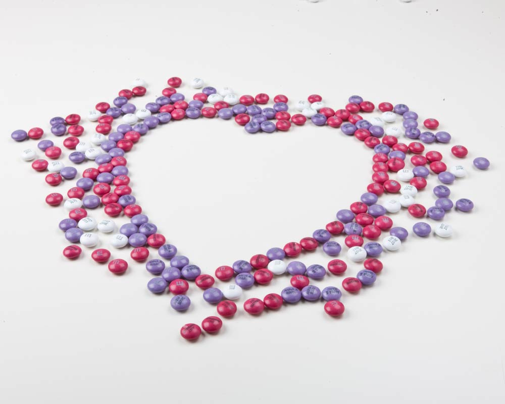 Personalised M&M'S arranged on a solid colour background in the shape of a heart
