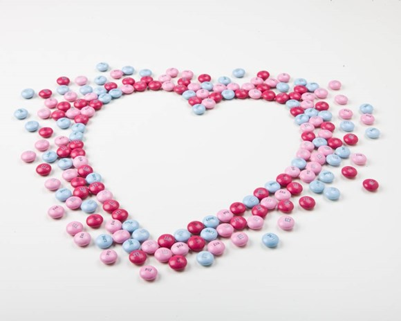 Pink, red, and blue customised M&M'S arranged on a white background in the shape of a heart