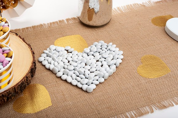 White personalised M&M'S arranged on a table in the shape of a heart