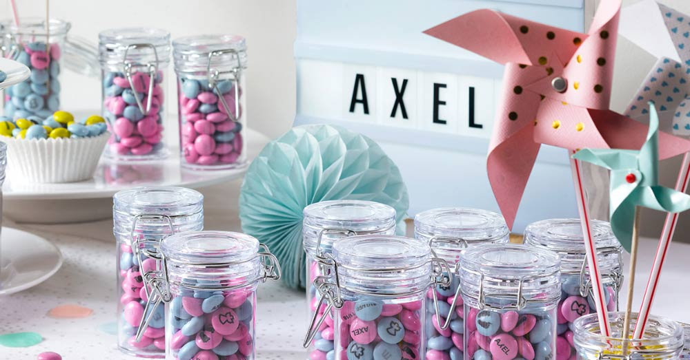 Pink and blue personalised M&M'S in glass jars with flip-top lids next to paper pinwheels